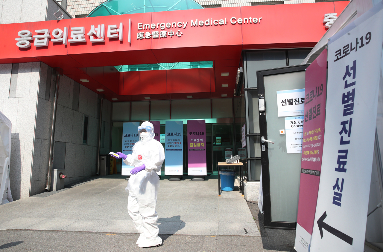 A worker stands outside a makeshift clinic for COVID-19 tests at the National Medical Center in Seoul on Wednesday. (Yonhap)