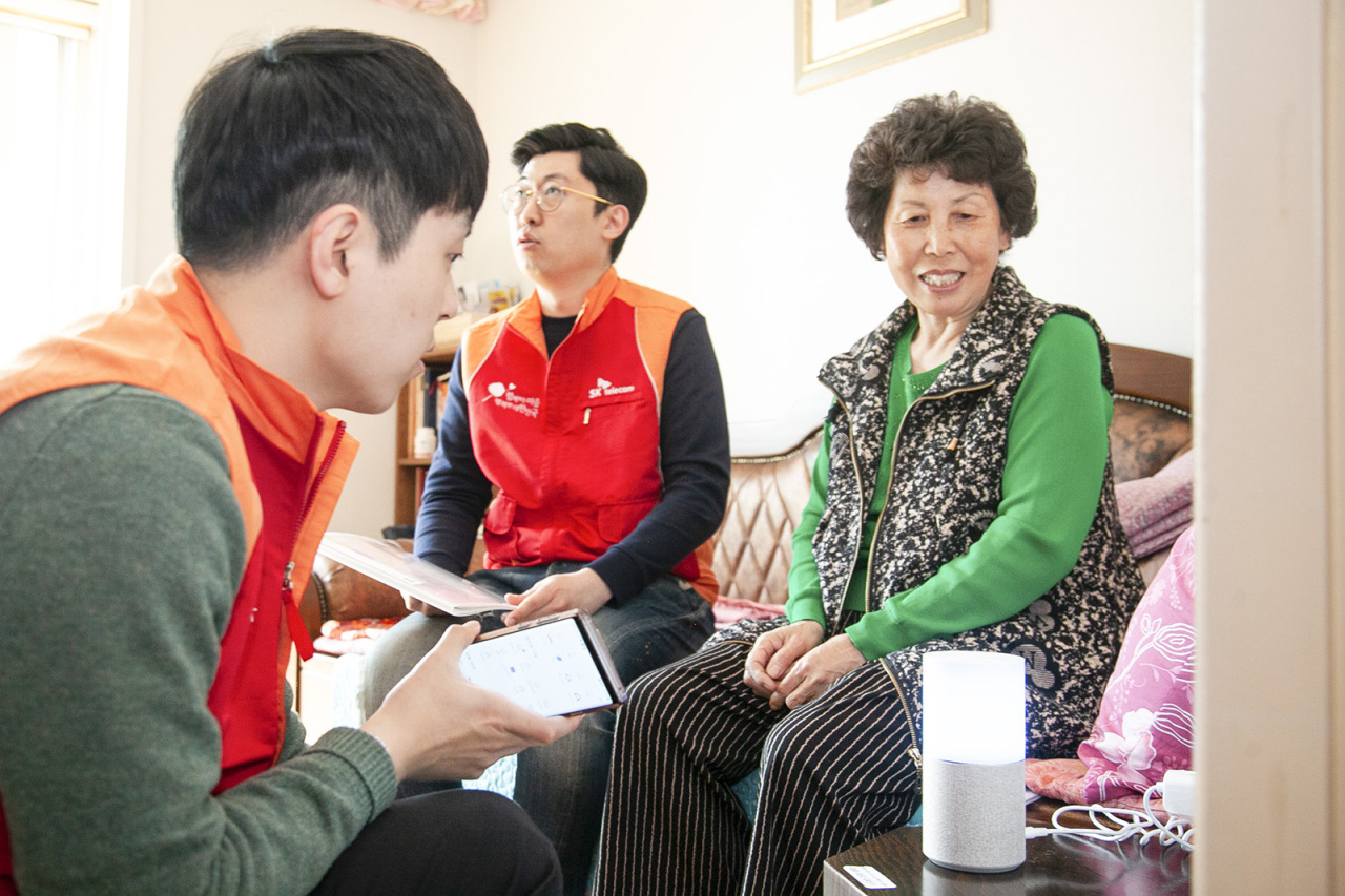 An SK Broadband employee explains to senior citizens how to operate the company's artificial intelligence speaker, Nugu. (SK Telecom)