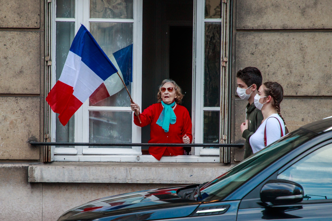A couple wearing protectives face masks pass by a building where a woman holds a French flags as the neighbors applaud every evening at 8pm from their windows to support French medical staff amid the ongoing coronavirus COVID-19 pandemic in Saint Mande, near Paris, France, 02 May 2020. (AFP-Yonhap)