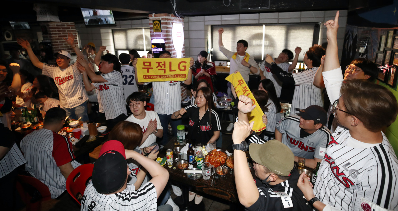 Fans of the LG Twins cheer on the team during the KBO Opening Day, on Tuesday in a pub in Seoul. (Yonhap)