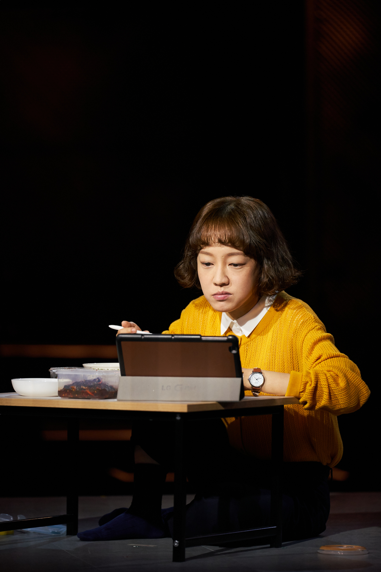 """Table for One"" begins with character O In-yong eating by herself while watching a reality show on a tablet PC. (Doosan Art Center)"