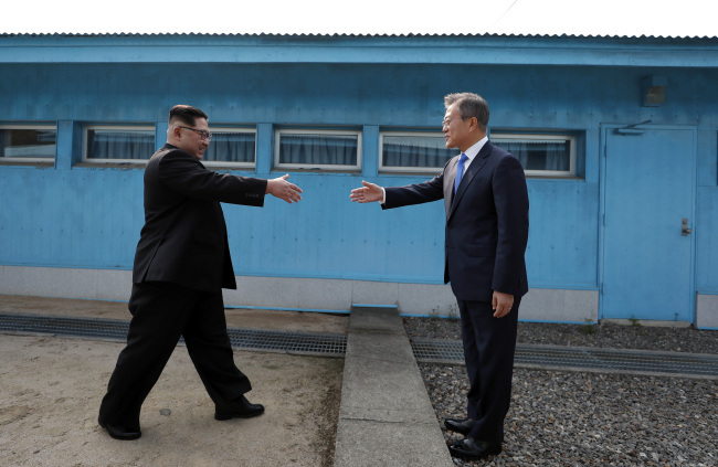 North Korean leader Kim Jong-un meets South Korean President Moon Jae-in at the military demarcation line at Panmunjom in the demilitarized zone in April 2018. (Yonhap)