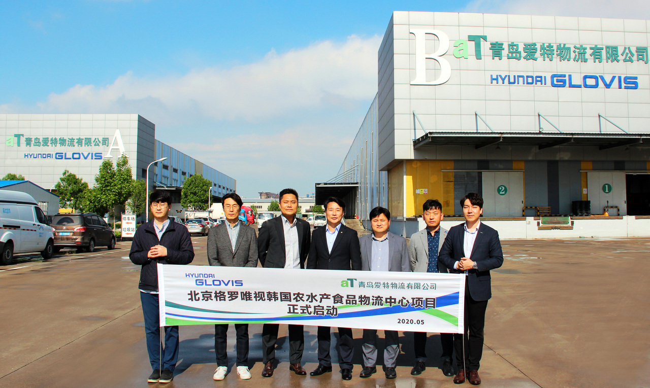 Beijing Glovis' Qingdao branch head Park Sang-won (third from left) and Korea Agro-Fisheries & Food Trade Corp.'s Qingdao branch head Lee Sang-gil (fourth from left) pose for a photo with officials. (Hyundai Glovis)