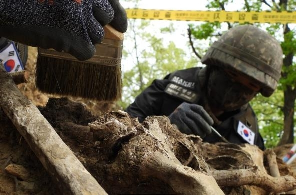 Service members carry out excavation work looking for remains of soldiers killed during the 1950-53 Korean War inside the Demilitarized Zone (DMZ) in this photo provided by the defense ministry on May 14, 2020. (Yonhap)