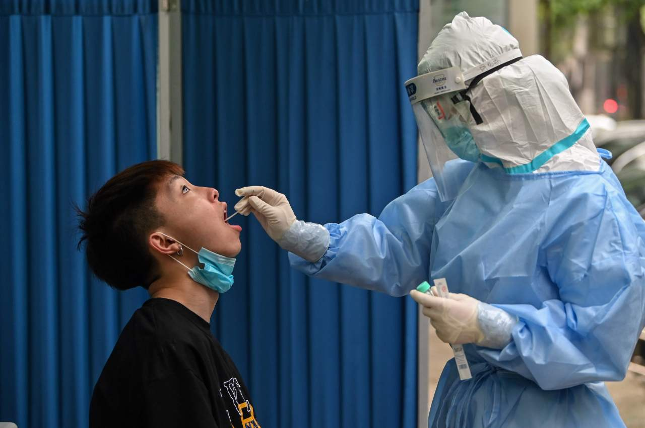 A medical worker takes a swab sample from a man to be tested for the COVID-19 novel coronavirus in Wuhan, in China?s central Hubei province on May 14, 2020. (AFP-Yonhap)