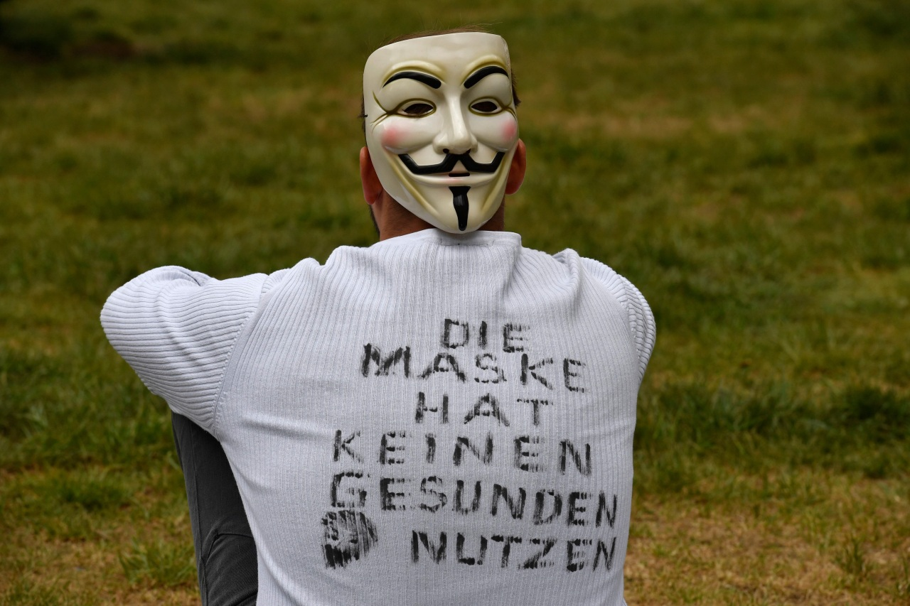A demonstrator wearing a mask and a T-shirt with inscriptions reading 'The mask has no healthy use' sits in the demo area during a protest against the Corona restrictions in Berlin on May 2, 2020, amid the new coronavirus COVID-19 pandemic.(AFP)