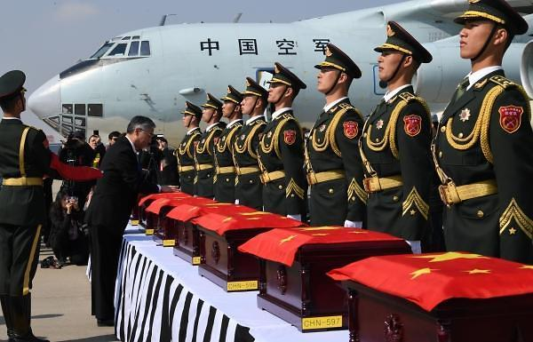 Chinese Ambassador to South Korea Qiu Guohong drapes a Chinese flag over a box containing the remains of a Chinese soldier killed in the 1950-53 Korean War at Incheon International Airport, west of Seoul, on April 3, 2019. (Yonhap)