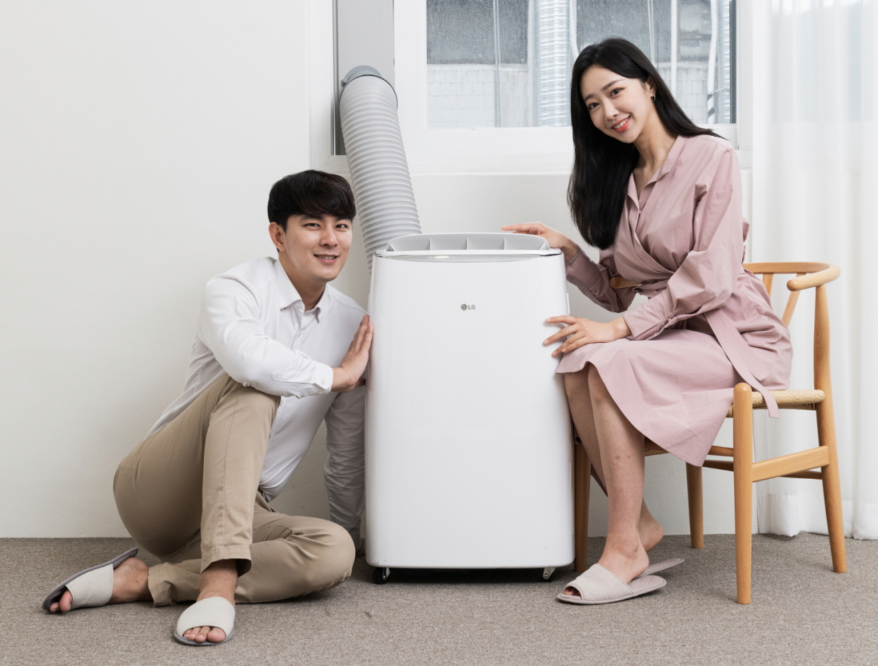 Models showcase a portable air conditioner. (LG Electronics)