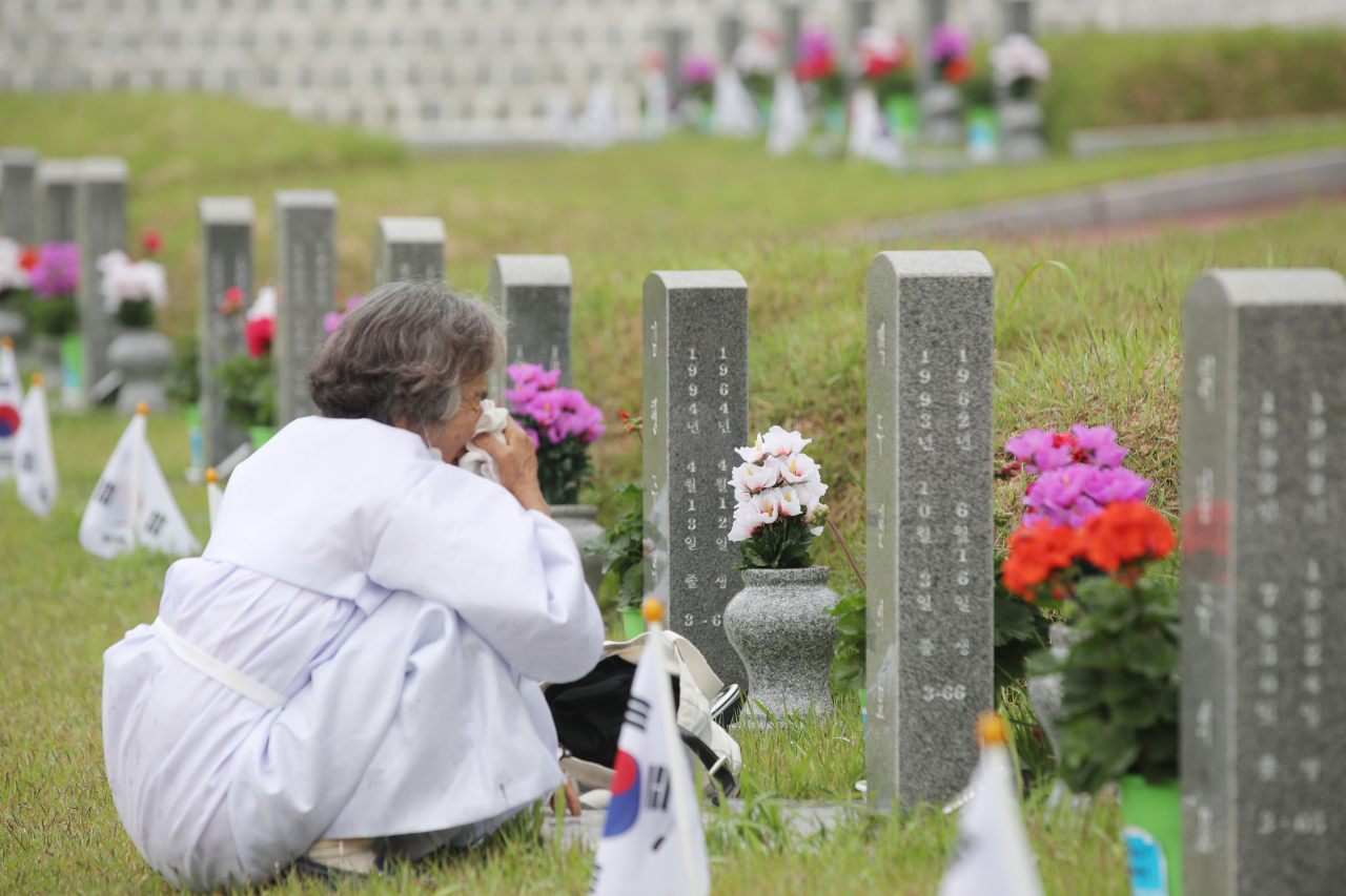 A woman sobs at a grave at a national cemetery honoring those killed in the 1980 Gwangju Democractic Uprising in Gwangju on Sunday, on the eve of its 40th anniversary. (Yonhap)