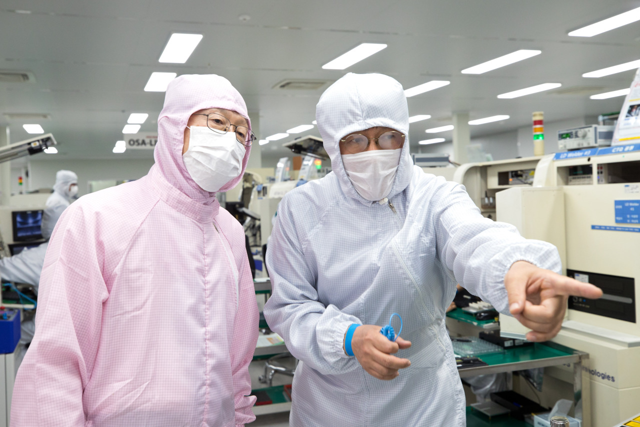 ICT Minister Choi Ki-young (left) listens to an OE Solutions' official explaining about the company's optical transceiver at its production line located in Gwangju, South Jeolla Province, Monday. (Yonhap)