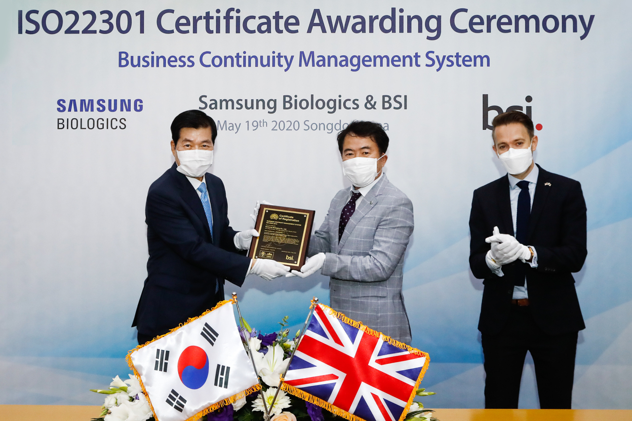 Samsung Biologics CEO Kim Tae-han (left), BSI Korea lead auditor Song Kyung-soo (center) and the British Embassy's Economic and Prosperity Counselor Mark Buttigieg pose with the ISO22301 certificate on Tuesday at Samsung Biologics headquarters in Songdo, Incheon. (Samsung Biologics)