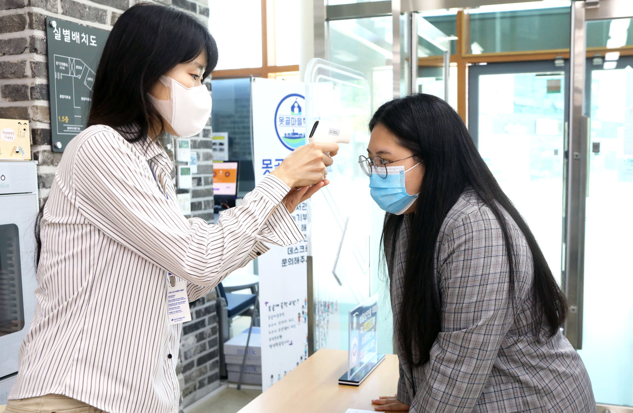 A visitor is thermal screened before entering a library in Gangnam, Seoul. (Yonhap)