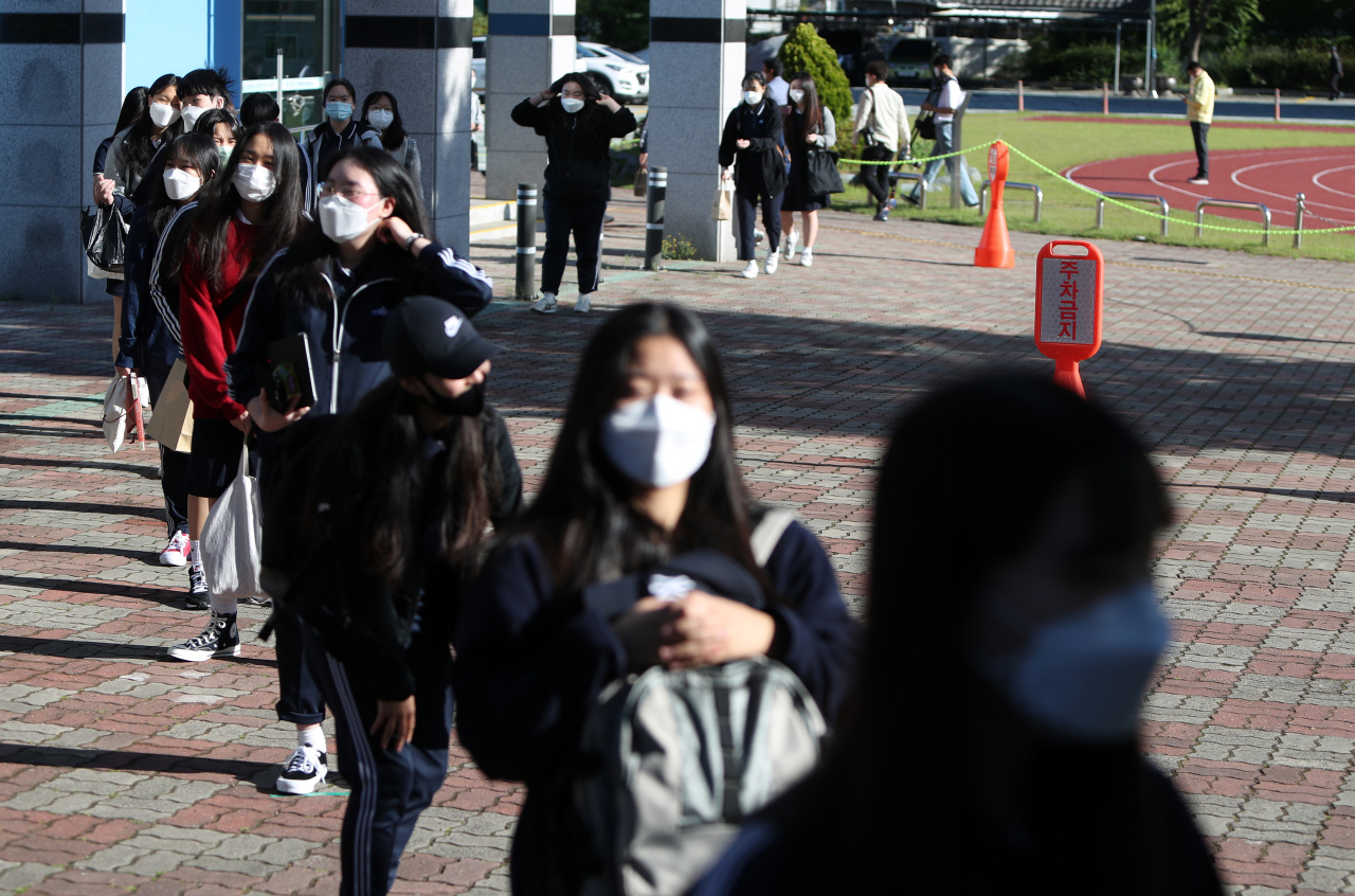 High school seniors line up outdoors to get their temperatures checked before entering the building at a girls' high school in Daegu on Wednesday. (Yonhap)