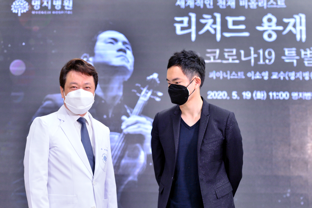 Myongji Medical Foundation Chairman Lee Wang-jun (left) and violist Richard Yongjae O'Neill exchange words after a concert held at Myongji Hospital in Goyang, Gyeonggi Province, on Tuesday. (Park Hyun-koo/The Korea Herald)