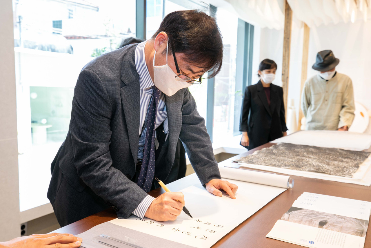 Vice Culture Minister Oh Young-woo writes on a guestbook during an opening ceremony of the Hanji Cultural Industry Center in Seoul on Wednesday. (HCIC)