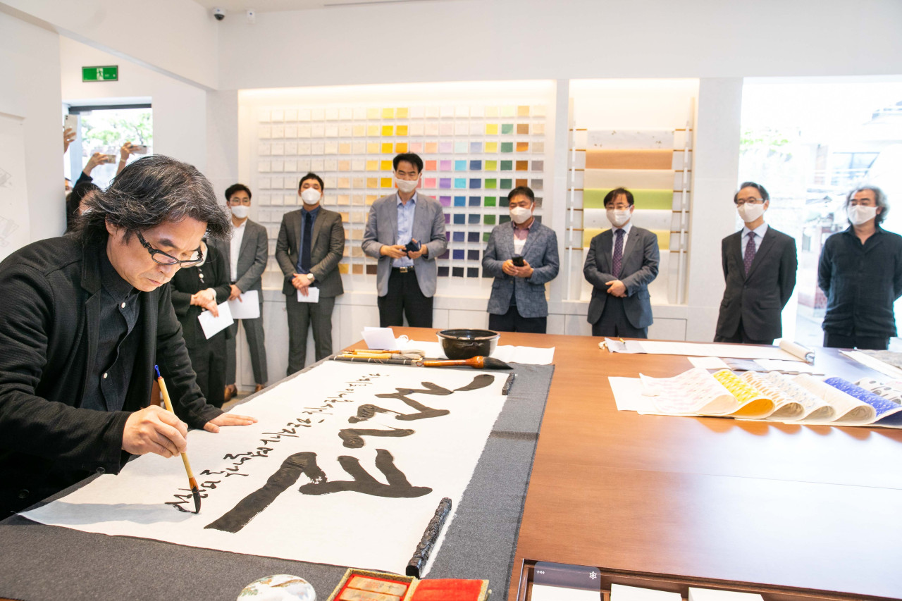Kang Byung-in, a calligraphy artist, writes on Korean traditional paper hanji during an opening ceremony of the Hanji Cultural Industry Center in Seoul on Wednesday. (HCIC)