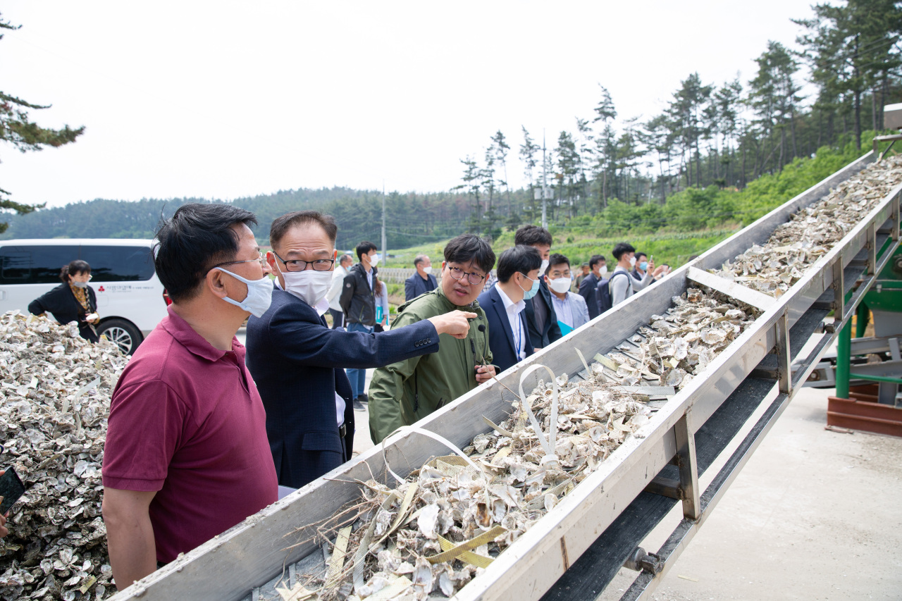 A Kowepo official (second from left) explains the operation of an oyster shell recycling facility. (Kowepo)