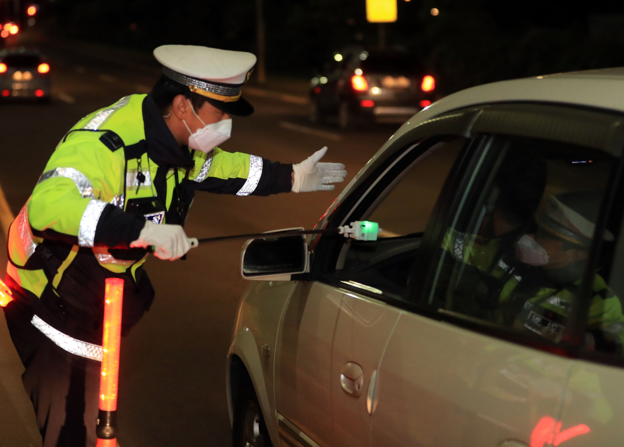A Jeju policeman uses a non-contact DUI testing device at a check point in Jeju on May 20. (Yonhap)