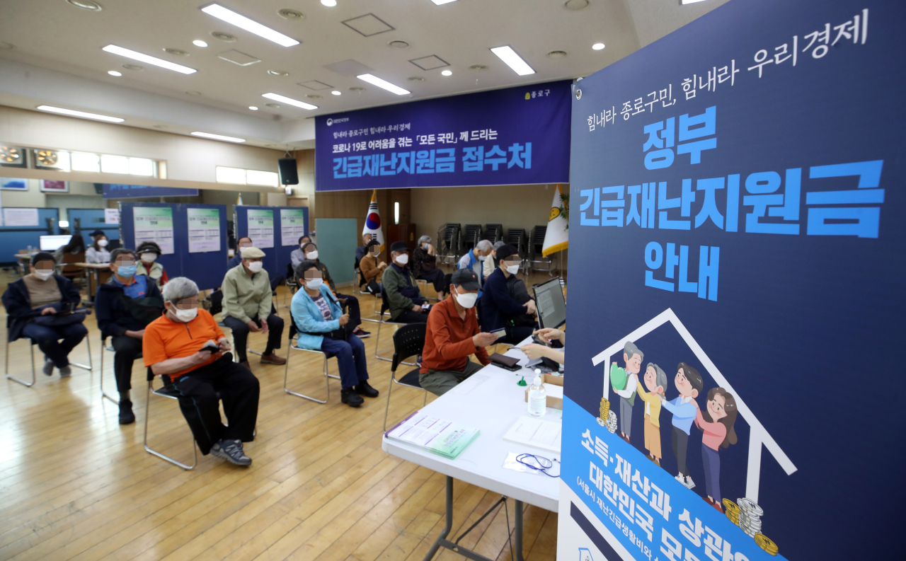 People wait at a community service center in Seoul`s Jongno Ward last week to apply for the government`s emergency relief funds. (Yonhap)