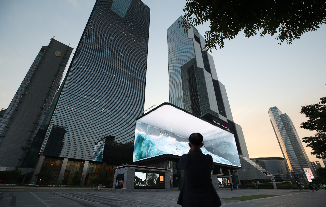 """A passerby films the """"Wave"""" at Coex K-Pop Square, Samseong-dong, Seoul, on Monday evening. (Yonhap)"""