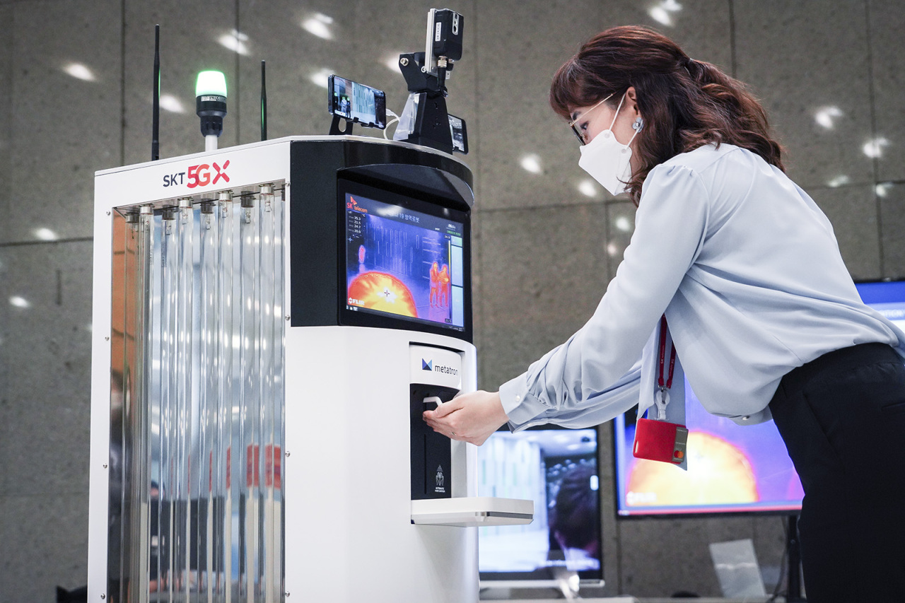 VIRUS-FIGHTING ROBOT -- A robot dispenses hand sanitizer to a SK Telecom employee at the company's headquarters on Tuesday. SKT said it has collaborated with Omron Korea to develop the robot as an epidemic preconvention measure. The robot, equipped with artificial intelligence, self-driving technology and other IoT features, can check temperatures of people moving in and out of the building and send data to the company's server to control potential viral infection. The robot can also recognize if a person is wearing a mask via image recognition technology and recommend the person to wear it otherwise. SKT plans to officially commercialize the robot during the second half this year. (Yonhap)