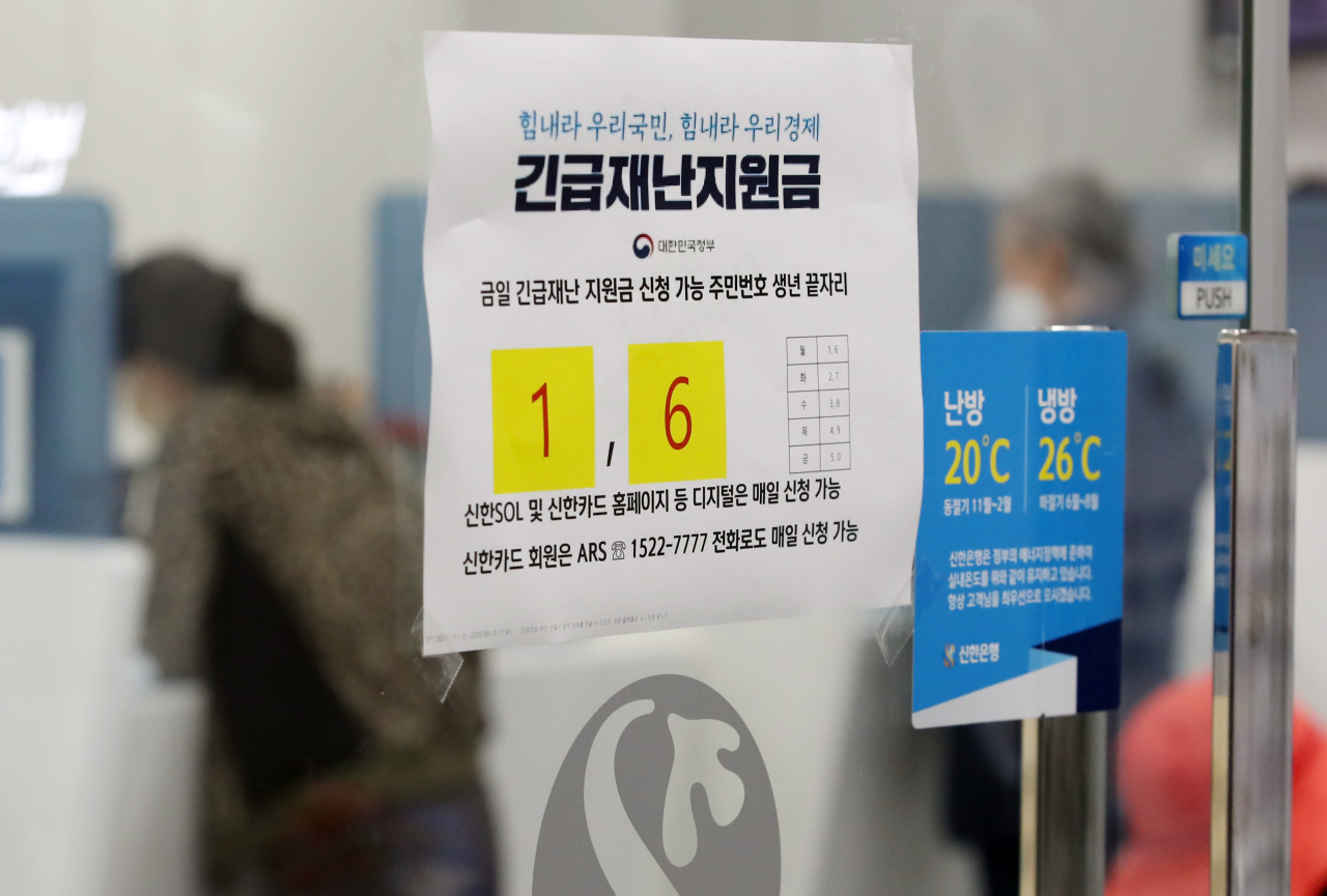 A notice attached to the door of a local bank`s branch in Seoul shows how citizens can receive disaster relief emergency funds, aimed at supporting coronavirus-hit housholds. (Yonhap)