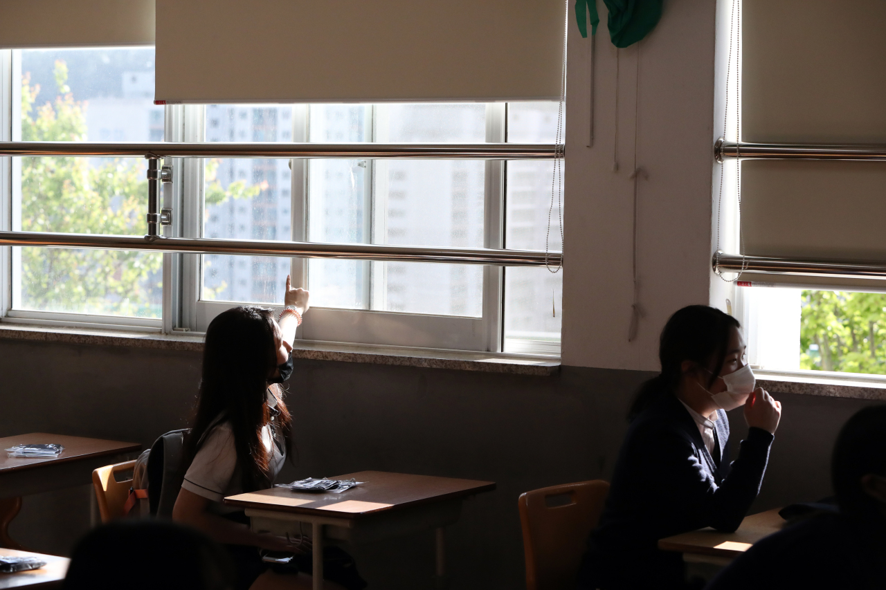 A student opens a classroom window May 20. (Yonhap)