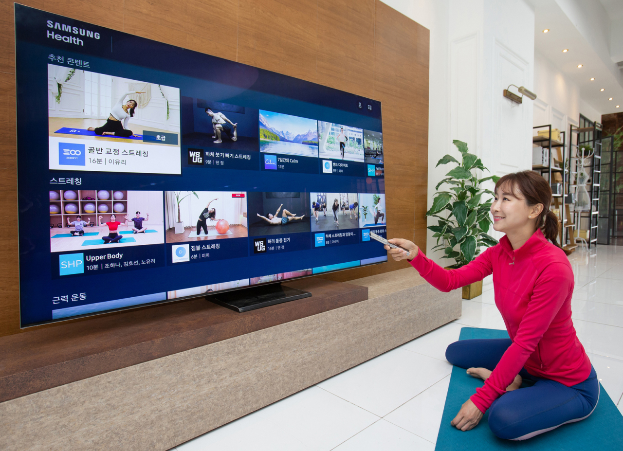 A model selects a home-training program on a Samsung TV at home via Samsung Health. (Samsung Electronics)