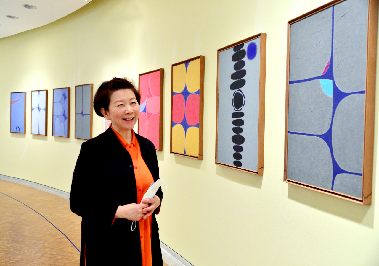 Park Mee-jung, director of Whanki Museum, poses in front of Kim Whan-ki's artworks. (Park Hyun-koo/The Korea Herald)