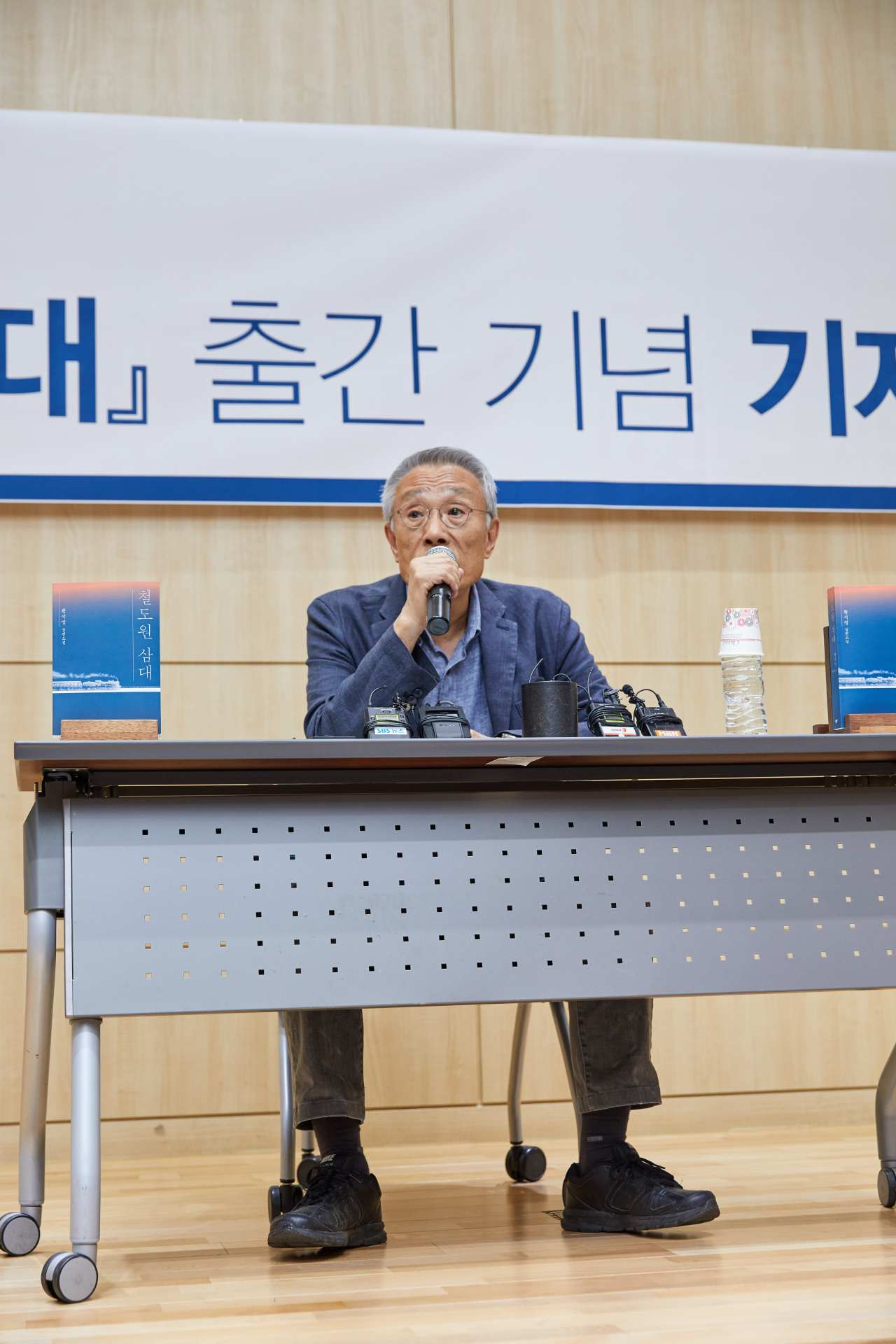 """Hwang Sok-yong talks during a press conference on his new novel """"Three Generations of Railworkers"""" held in Seoul on Tuesday. (Changbi)"""