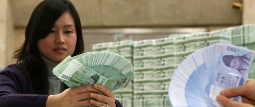 Commercial bank employees look at a batch of fresh bills. (Yonhap)