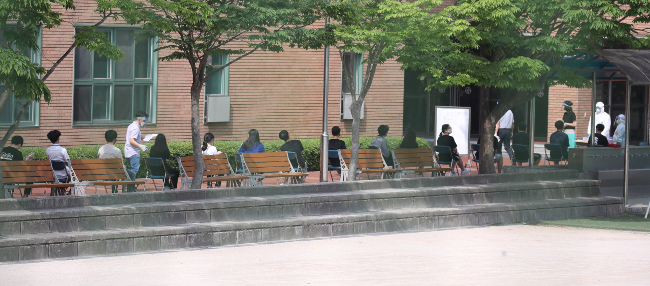 Students and staff members at a high school in Seoul wait in line to undergo COVID-19 testing Monday, after a 19-year-old student tested positive over the weekend. (Yonhap)
