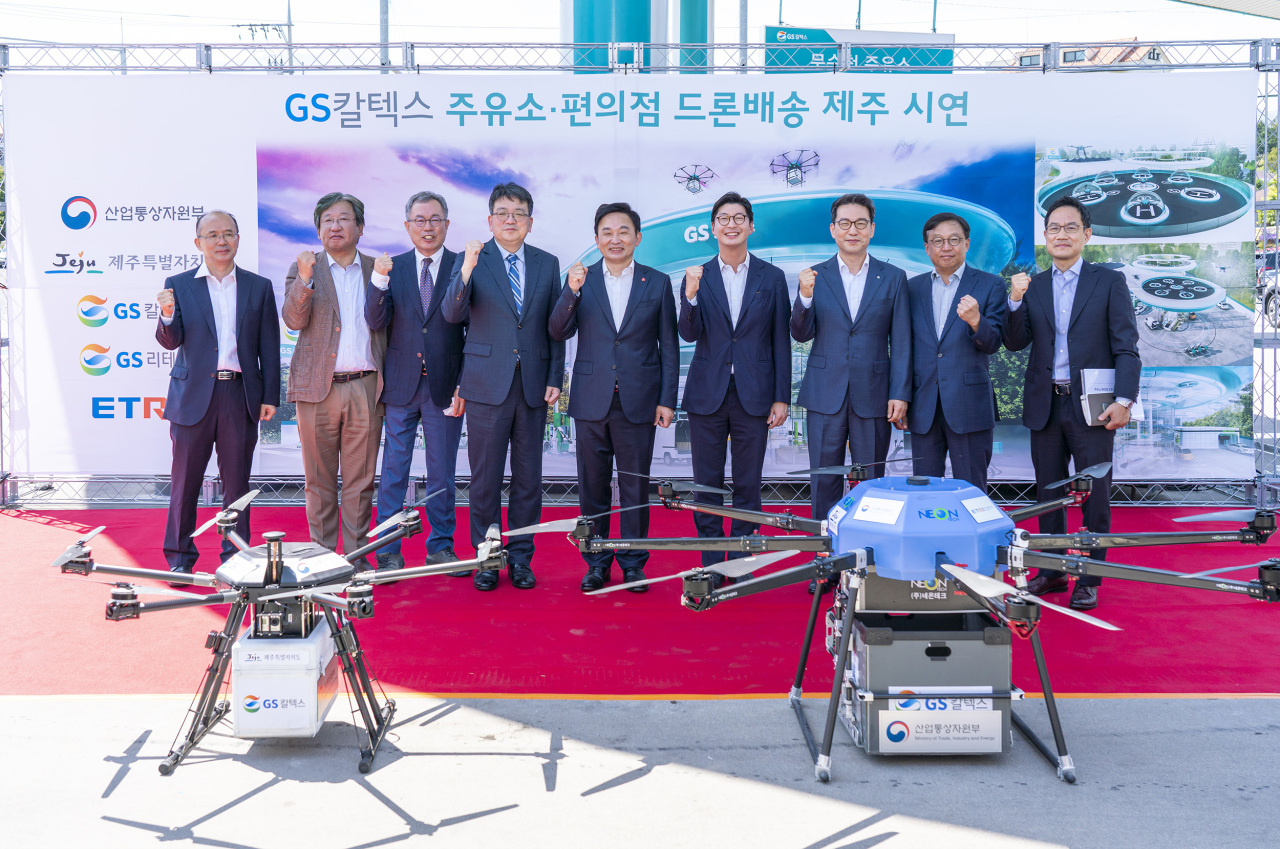 Jeju Province Gov. Won Hee-ryong (fifth from left), GS Caltex CEO Hur Sae-hong (sixth from left) and GS Retail President Cho Yoon-sung (seventh from left) pose at a drone delivery test event held Monday on Jeju Island. (GS Caltex)