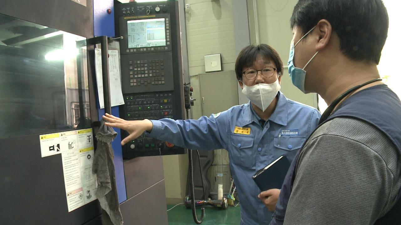 A Posco employee (left) explains a factory monitoring system to a molding firm CEO. (Posco)