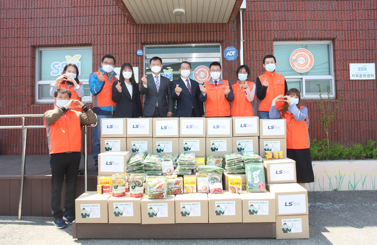 Employees pose a photo after delivering food and household goods to those in need. (LS Cable & System)