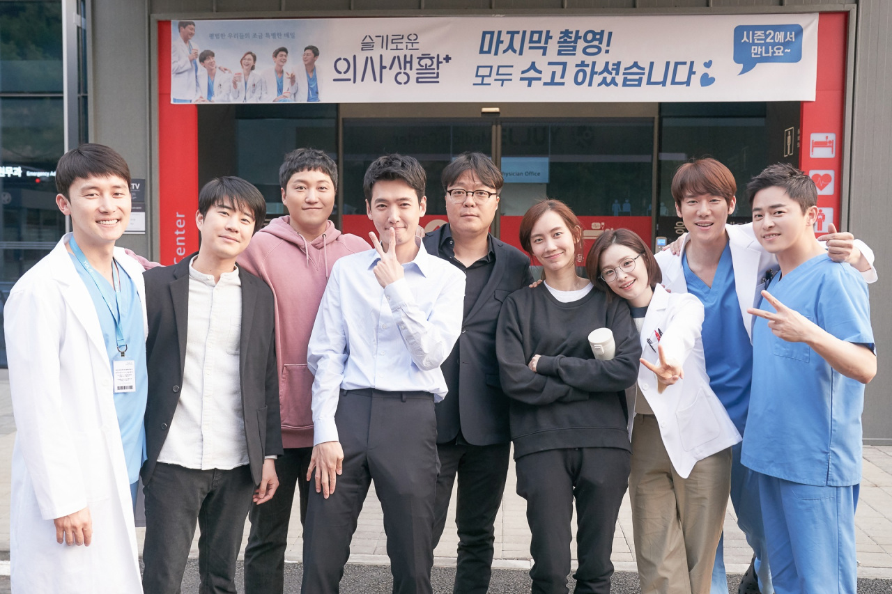 "Producer Shin Won-ho (center) of tvN's ""Hospital Playlist"" poses with lead actors of the series. (tvN)"