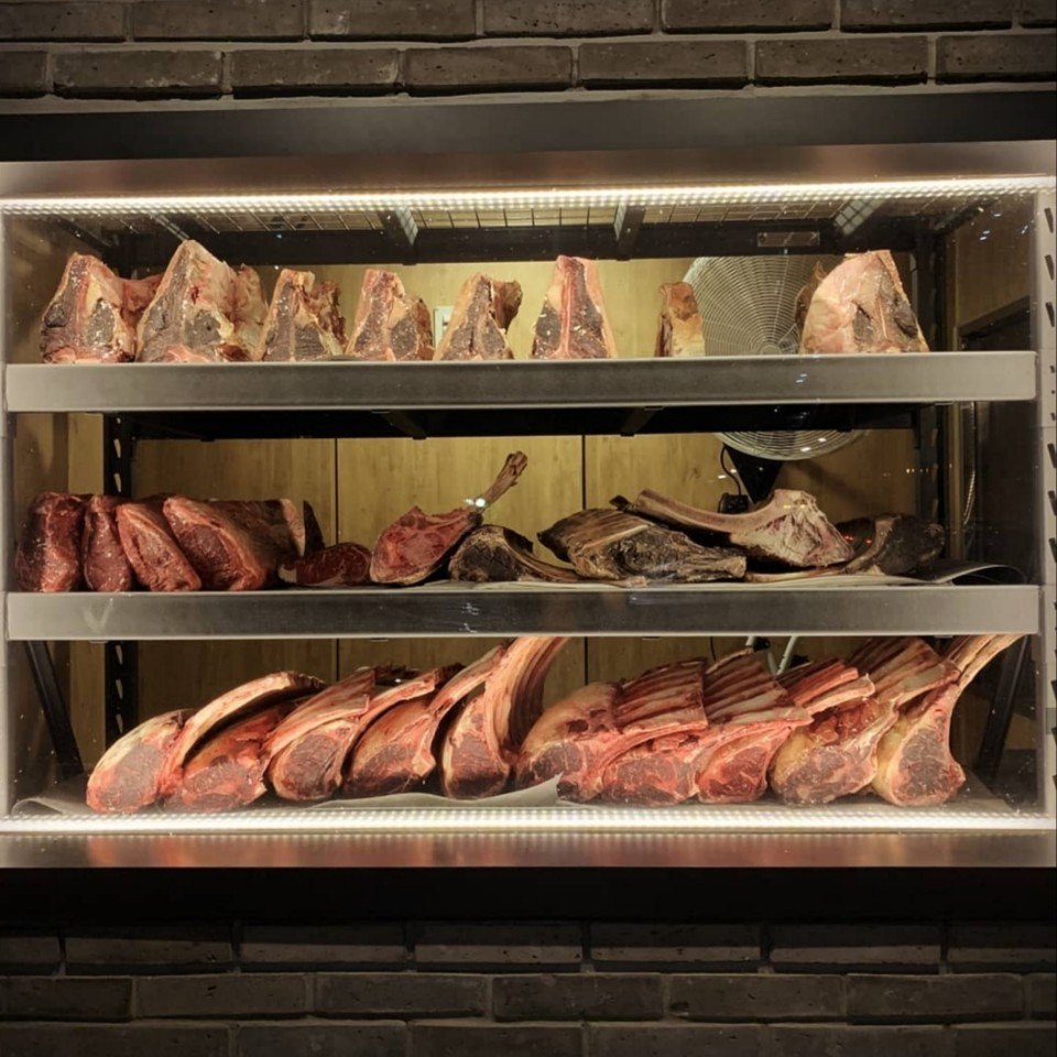 During dry aging, beef is left naked in a controlled environment allowing natural enzymes to break down connective tissue for a softer steak. Moisture is also lost during the process leading to more concentrated beefiness (The Porterhouse Butcher and More)