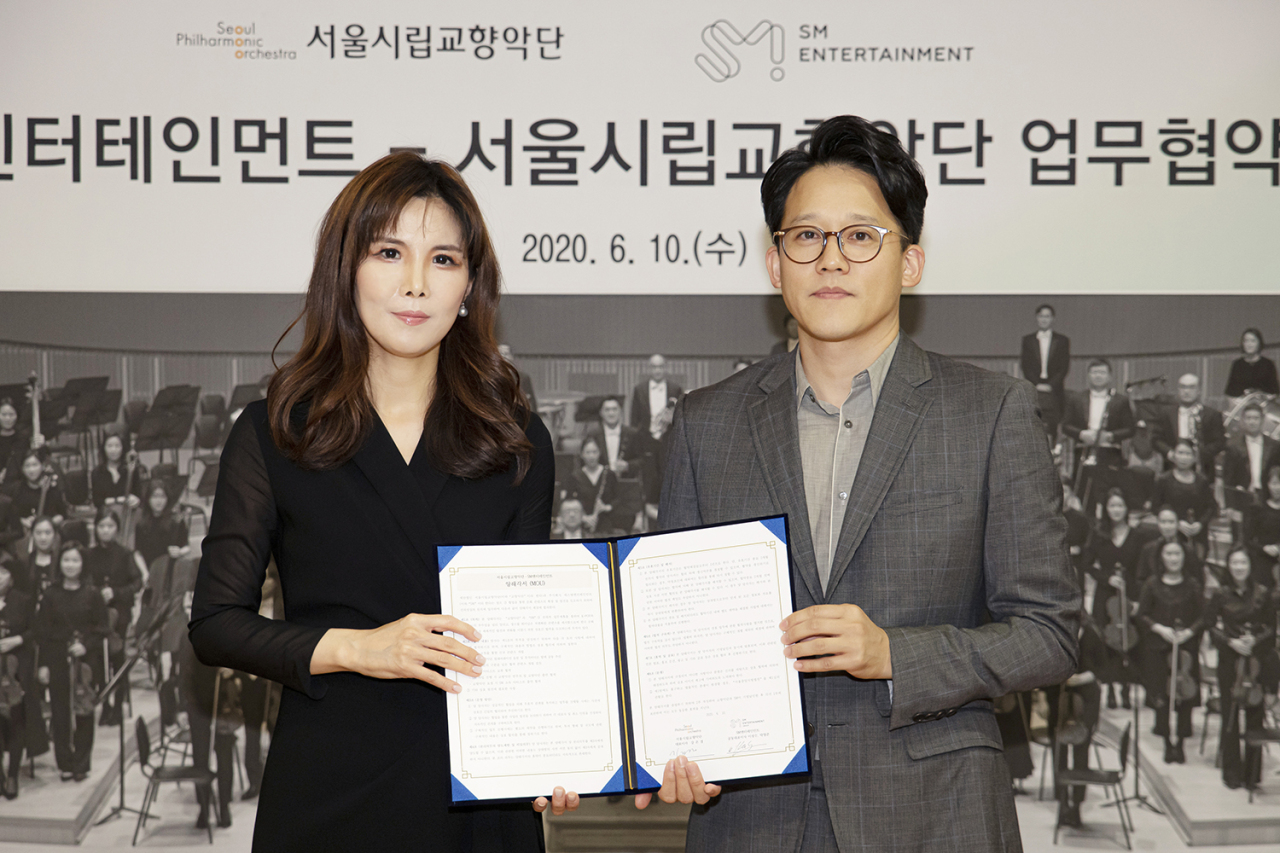 Kang Eun-kyung (left), CEO of the Seoul Philharmonic Orchestra and Lee Sung-soo, co-CEO of S.M. Entertainment, post for pictures after signing a memorandum of understanding Wednesday. (Seoul Philharmonic Orchestra)