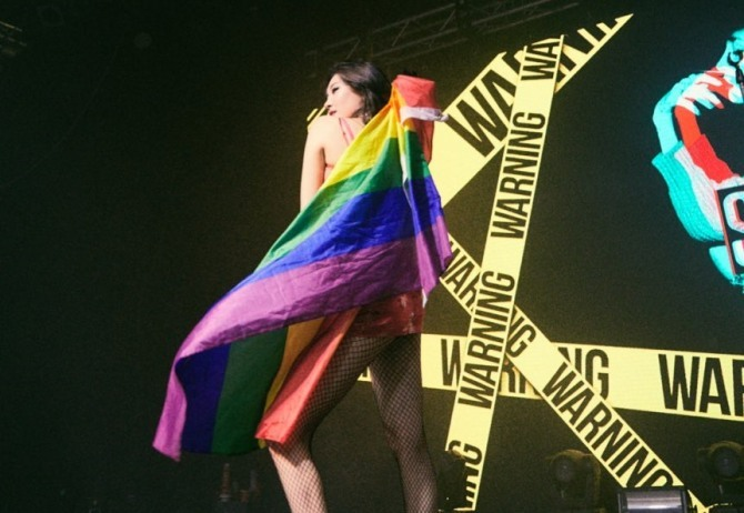 Sunmi poses on stage with a rainbow flag wrapped around her body while performing in Amsterdam. (Sunmi's Instagram)