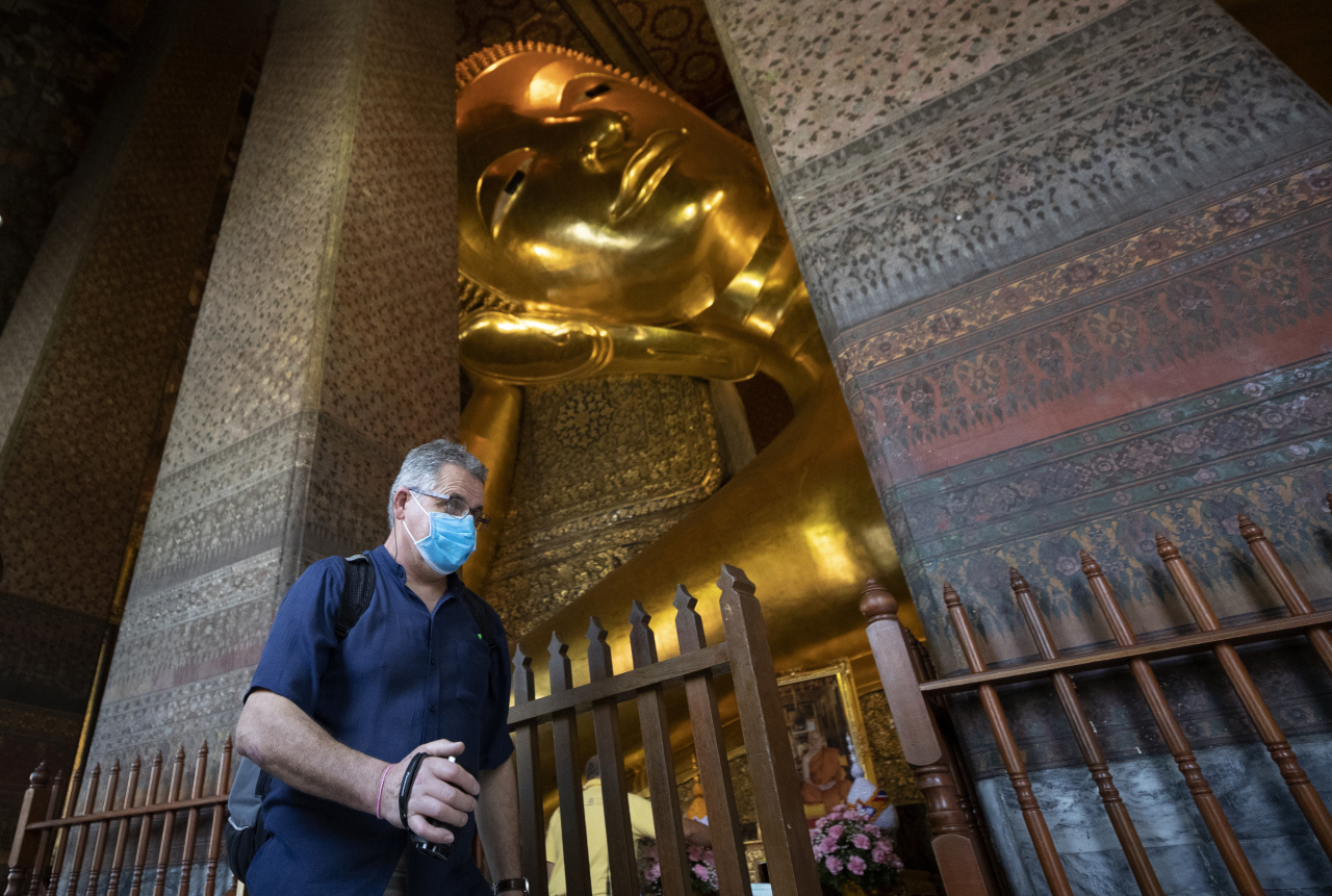 A tourist wearing protective mask walk in front of giant Buddha at Wat Pho temple in Bangkok, Thailand. (AP-Yonhap)