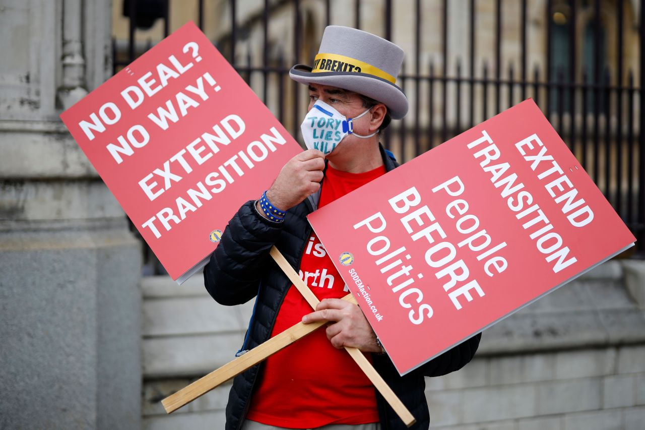 A demonstrator holds placards demanding extension of Brexit transition period outside the Houses of Parliament in London, Britain, on Wednesday. (AFP-Yonhap)