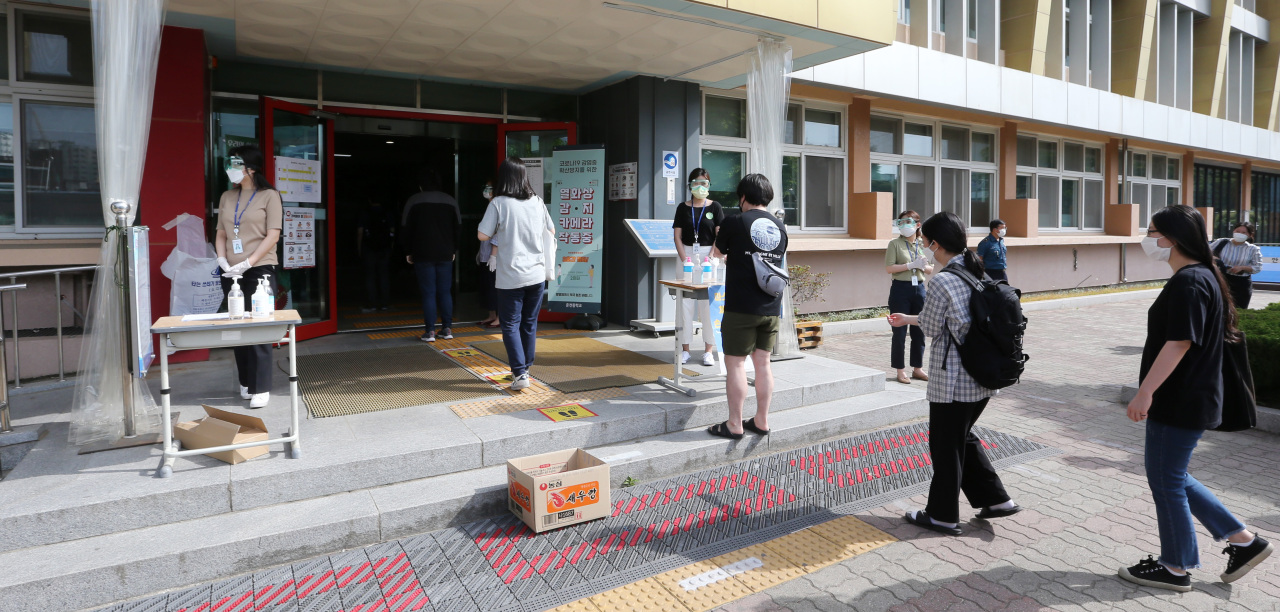 Applicants disinfect their hands before entering the test venue on Saturday. (Yonhap)