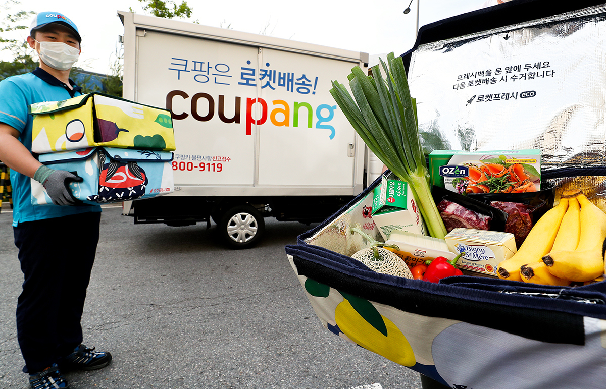 A Coupang employee delivers fresh groceries in a reusable cool bag. (Coupang)