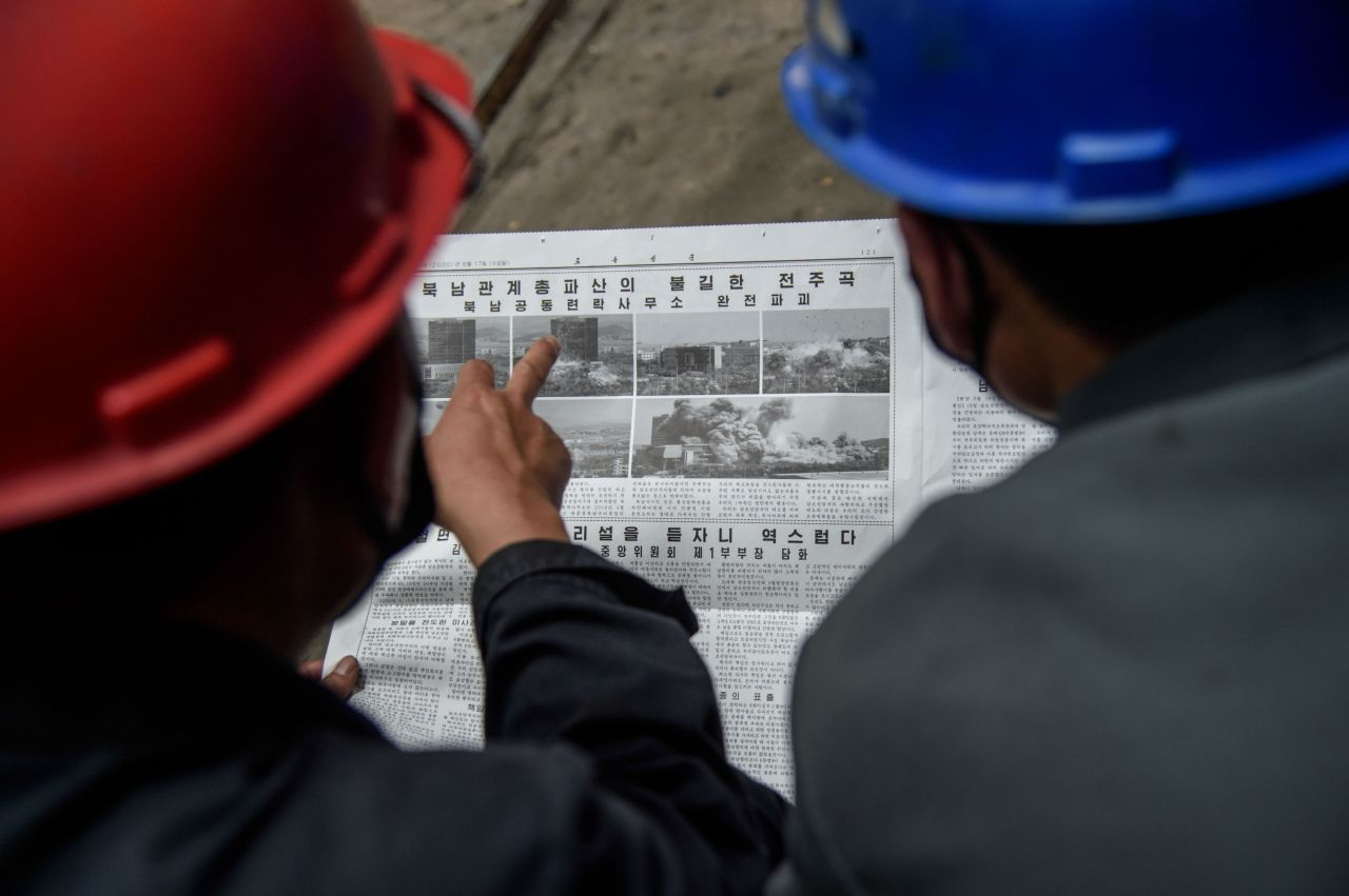Employees of the Kim Jong Thae Electric Locomotive Complex in Pyongyang read a copy of the Rodong Sinmun newspaper showing coverage of North Korea`s demolition of the north-south joint liaison office, on June 17, 2020. - North Korea`s spectacular destruction of its liaison office with the South is part of a series of staged provocations aimed at forcing concessions from Seoul and Washington, analysts say. (AFP-Yonhap)