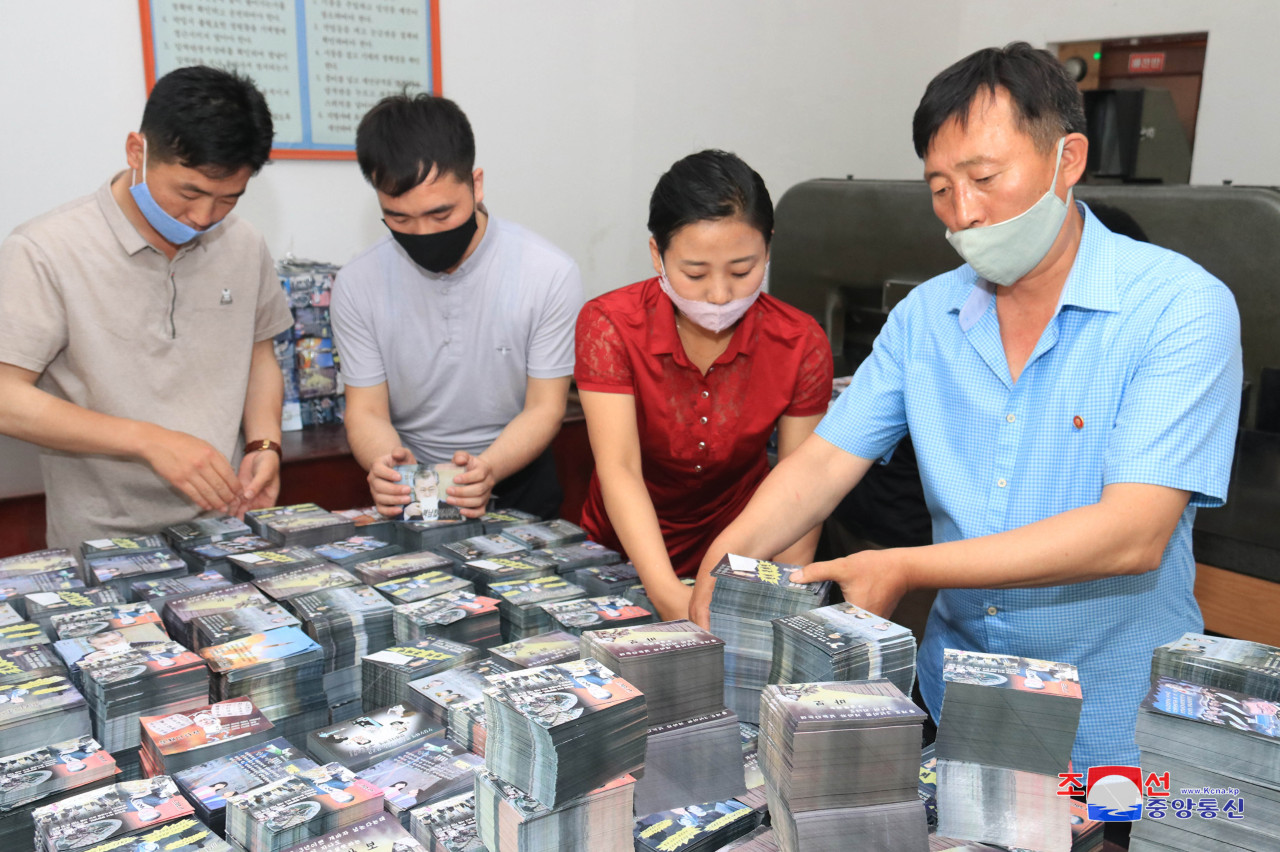 In this photo, North Koreans are preparing anti-Seoul leaflets at an undisclosed location.(KCNA-Yonhap)