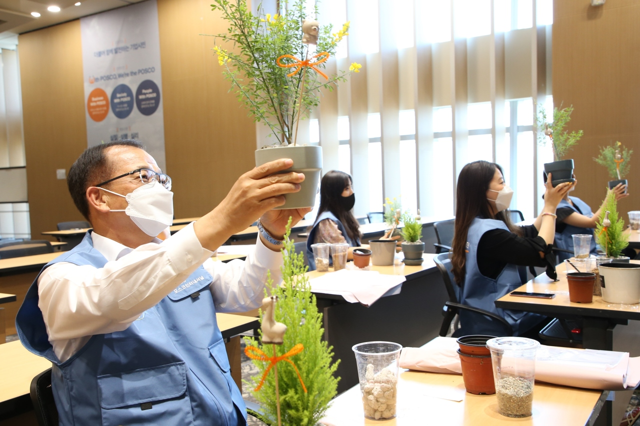 Posco International President Joo Si-bo (left) and students hold up their flowerpots in a flower arranging class organized by the company on Monday. (Posco International)