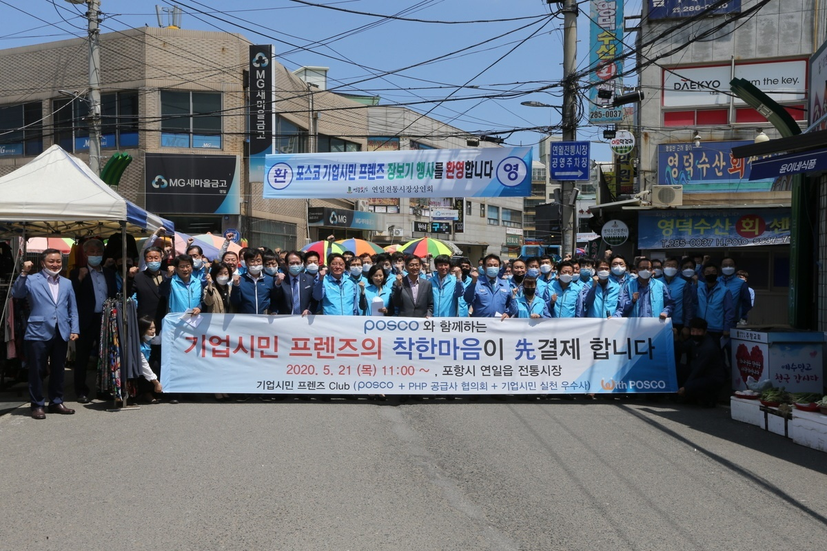 Employees of Posco Group and its partner companies pose in front of Yeonil Traditional Market in Pohang, North Gyeongsang Province, on May 21. (Posco)