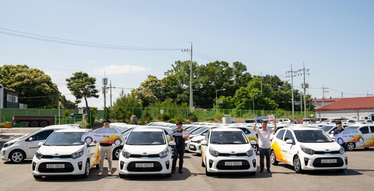 Hankook Tire employees pose next to cars that will be delivered to social welfare centers. (Hankook Tire)