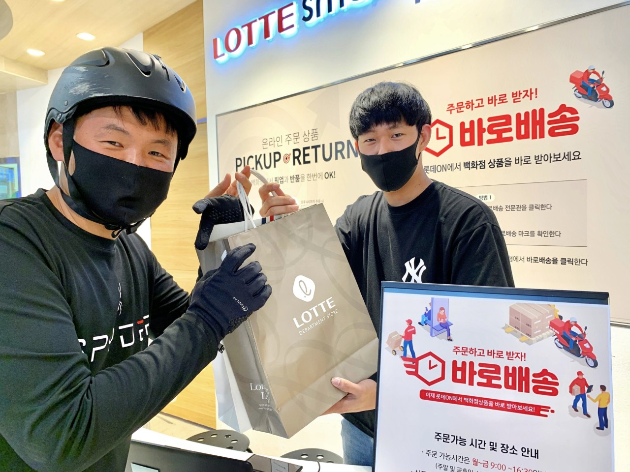 A delivery man receives a shopping bag from a Lotte Department Store employee, promoting the industry's first three-hour delivery service launched by it on Monday. (Lotte Department Store)