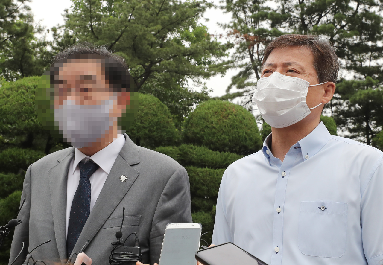 Park Jung-oh (right), head of Kuensaem, and his lawyer answer reporters' question after attending the Unification Ministry's hearing to decide the revocation of its operation permit on Monday in Seoul. (Yonhap)